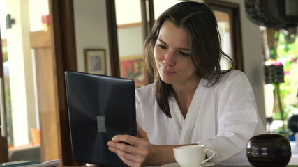 Woman with tablet computer sit by the table at home
