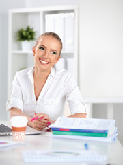 Woman working at office, sitting on the desk