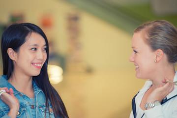 Asian and european pretty girls enjoying shopping in a mall