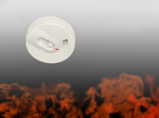 Photo of white smoke detector on ceiling. Illustrated flames.