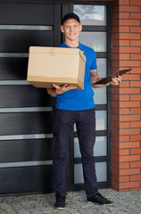 Smiling courier holding cardboard box