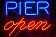A blue and red Pier Open sign