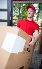 Delivery man holding a heavy box