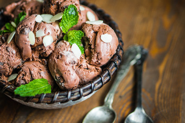 Chocolate ice cream with mint and almonds on wooden background