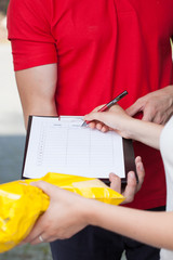 Woman signing document of delivered package