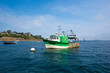 Green small fishing boat in shallow water - 68703308