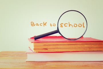 back to school background with stack of books and magnifying gla