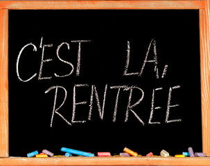 Back to school in french on black chalkboard and color pencils