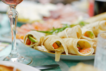 Pancake wraps with salmon and cucumber on a Russian festive tabl