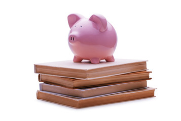 Piggy bank placed on the top of a pile of books