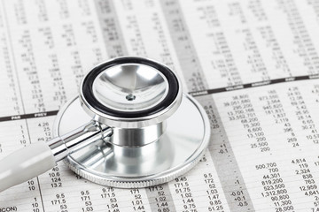 Stethoscope rest on stock price detail financial newspaper