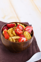 Cornflakes with strawberries  in bowl on table