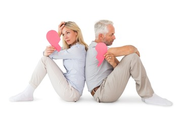 Unhappy couple sitting holding two halves of broken heart