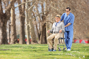 Male nurse pushing a senior in wheelchair outdoors