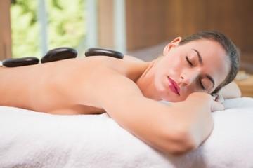 Beautiful woman receiving stone massage at health farm