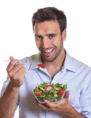 Lachender Mann ist frischen Salat
