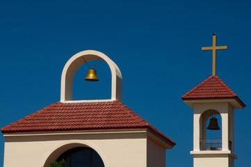Dach einer Kirche mit goldener glocke und Inri Kreuz