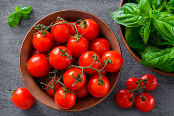 Tomatoes with basil in bowl on gray background