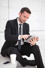 Portrait of an attractive businessman using a tablet
