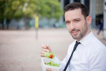 Businessman eating salad for lunch break