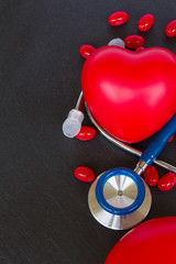 stethoscope with two red hearts and pills