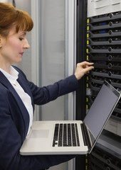 Pretty technician using laptop while working on servers