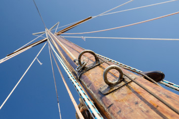 Old wooden mast with crosspieces and backstays, view from deck
