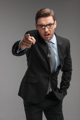 businessman angry and shouting over isolated grey background.