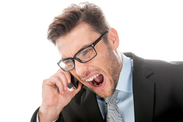 Angry businessman yelling into cellphone on white.