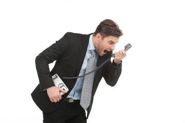Angry businessman yelling into landline phone on white
