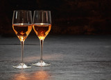 Two wine glasses standing on stone surface