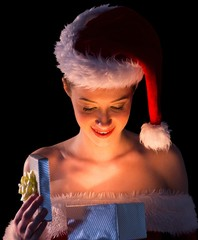 Pretty woman in santa outfit opening a gift smiling at it