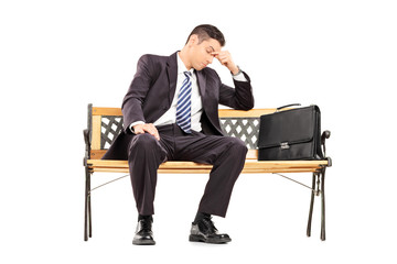 Tired businessman sitting on a bench