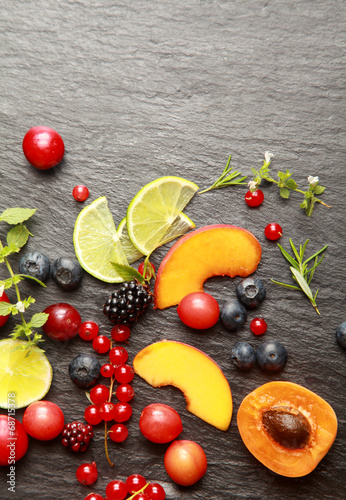 Leinwanddruck Bild Fresh fruit and herbs on a slate background