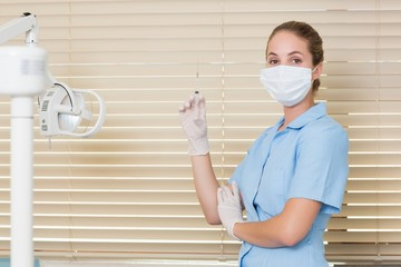 Dental assistant holding injection looking at camera