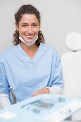 Dentist smiling at camera beside chair
