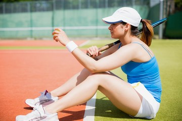 Pretty tennis player sitting on court