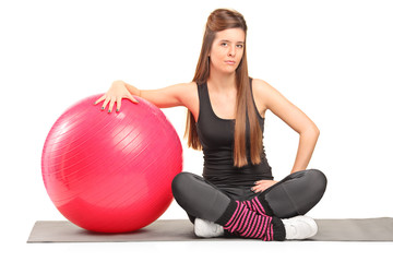 Female fitness instructor sitting on an exercising mat
