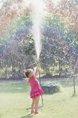 Dziewczynka w różowej sukience oblewająca się wodą