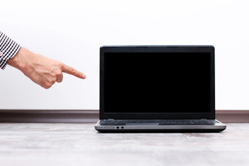 Closeup portrait of a male hand pointing on the laptop screen