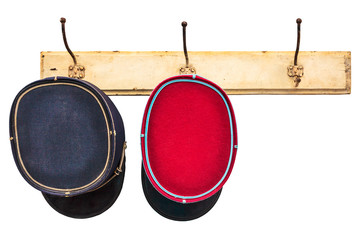 Two vintage conductor hats hanging on a hat-rack
