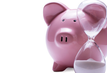 Egg timer next to a piggy bank, on white