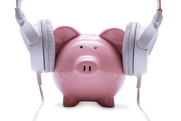 Funny piggy bank listening to stereo headphones