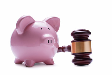 Piggy bank next to a wooden judge gavel