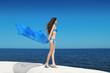 Enjoyment. Bikini model woman with blowing tissue over blue sky,