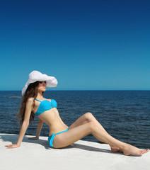 Sunbathing girl. Enjoyment. Slim bikini model woman in bikini ov