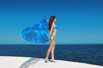 Enjoyment. Fashion model woman with blowing tissue over blue sky