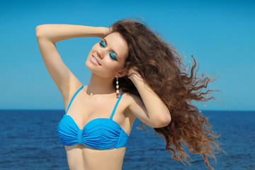 Beautiful woman smiling. Summer portrait over seaside and blue s