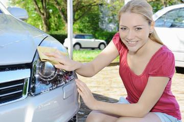 Frau reinigt Xenon-Scheinwerfer von Auto