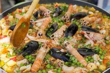 Stiring tasty organic paella with seafood and chicken breast